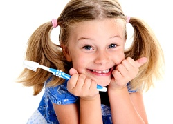 A little girl with pigtails smiling and holding a manual toothbrush