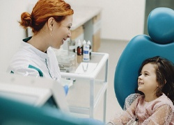 A little girl with dark hair smiling at a female dentist after having dental sealants applied